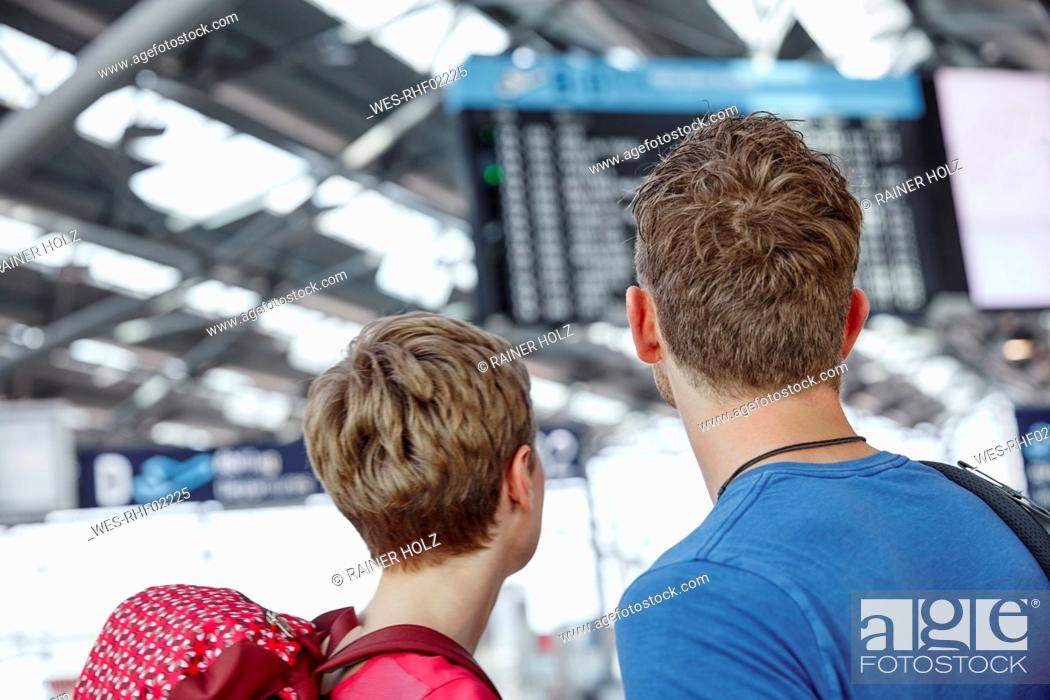 Stock Photo: Rear view of couple looking at arrival departure board at the airport.