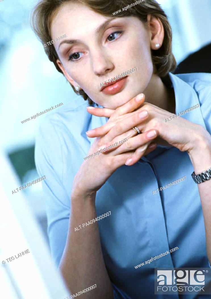 Stock Photo: Businesswoman with hands clasped under chin, close-up.