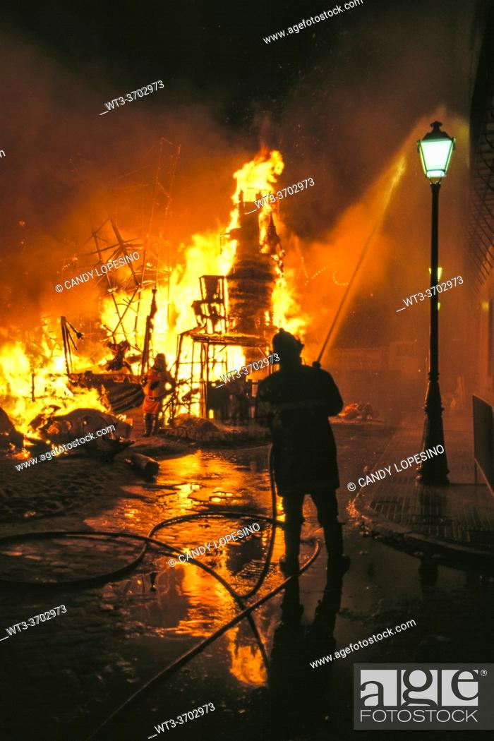 Stock Photo: Fallas festival, La Cremá, Nit del Foc, night of the fire, fireman extinguishing the burnt ninots, . VALENCIA, VALENCIAN COMMUNITY, SPAIN, EUROPE. .