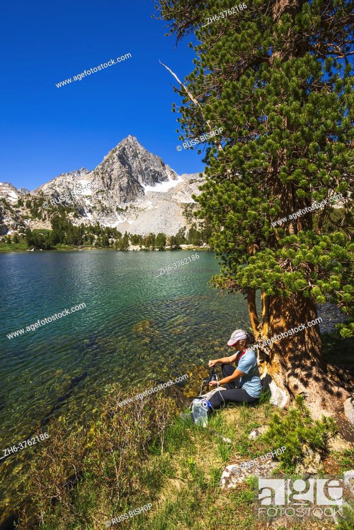 Imagen: Hiker purifying water on the shore of Treasure Lake, John Muir Wilderness, Sierra Nevada Mountains, California USA.