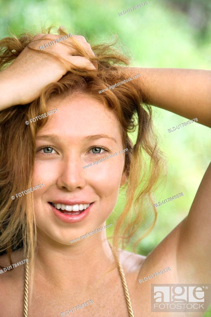 Stock Photo: Beautiful woman holding hair up while smiling and looking at viewer.