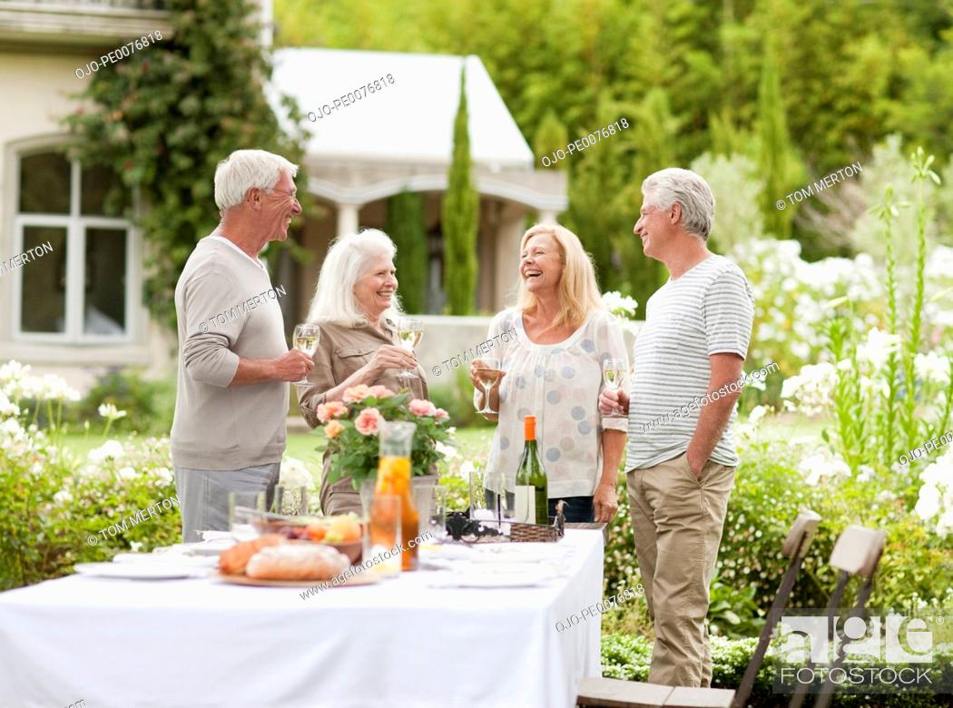 Stock Photo: Couples drinking wine in garden.