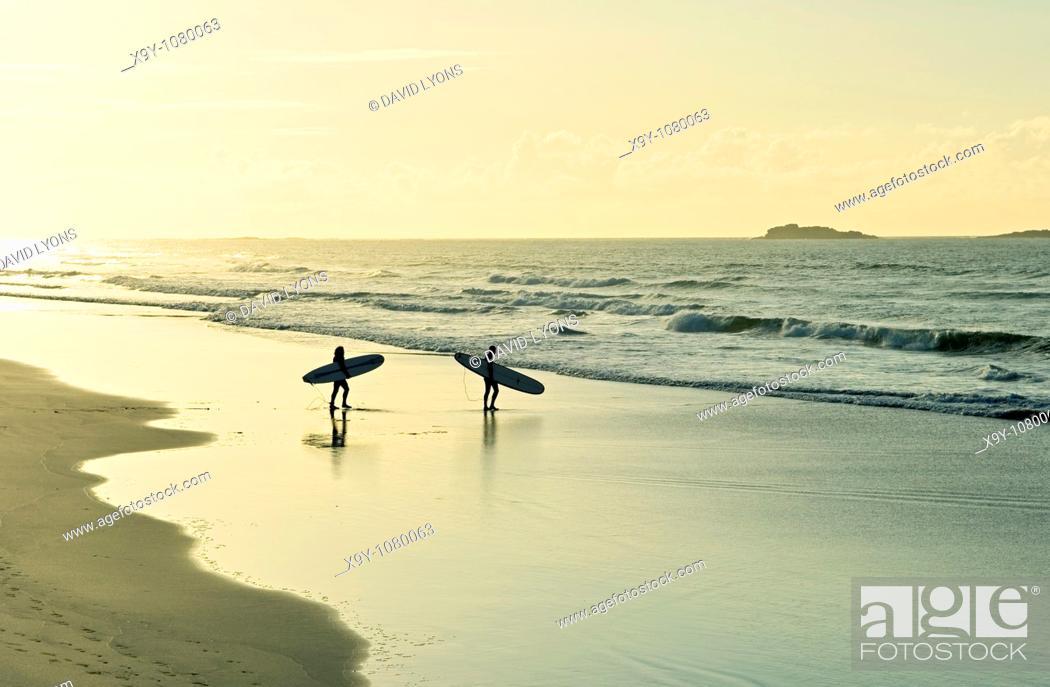 Stock Photo: Surfers carrying surfboards walking along sandy beach shoreline evening light summer  White Rocks Strand, Portrush, Ireland.