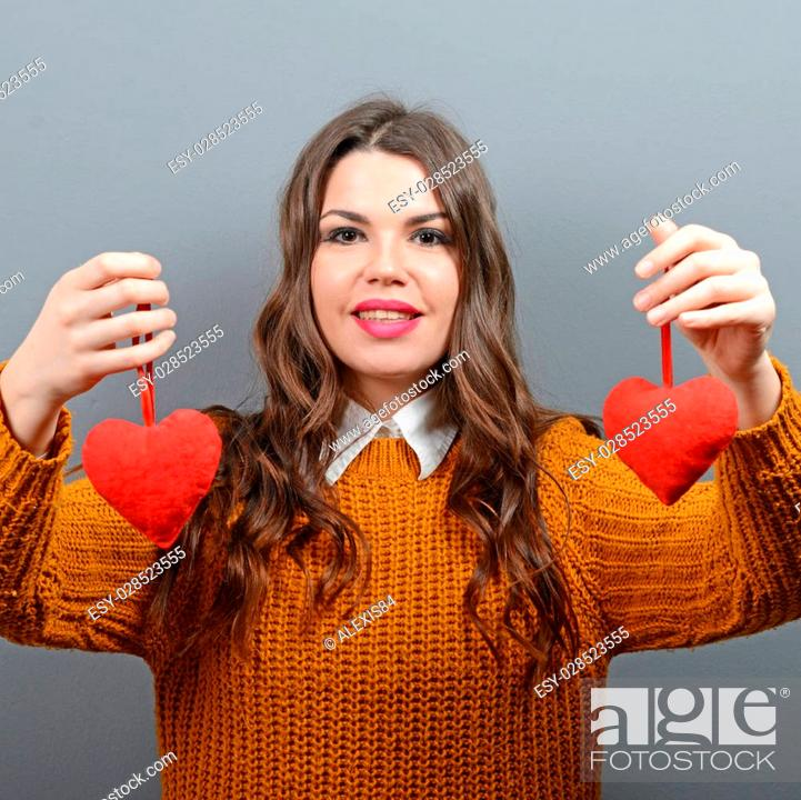 Stock Photo: Beautiful happy woman holding heart in hands against gray background.