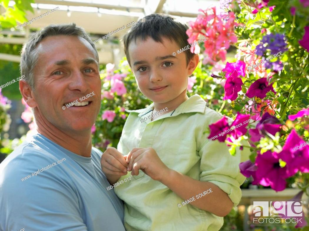 Stock Photo: Father holding son in garden centre.