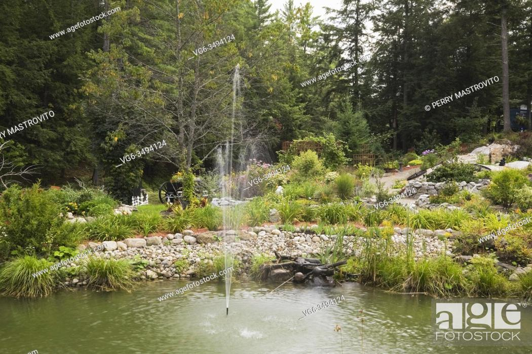 Stock Photo: Pond with water fountain jet spray and paths and borders planted with perennial plants, flowers and shrubs including Hemerocallis - Daylilies.