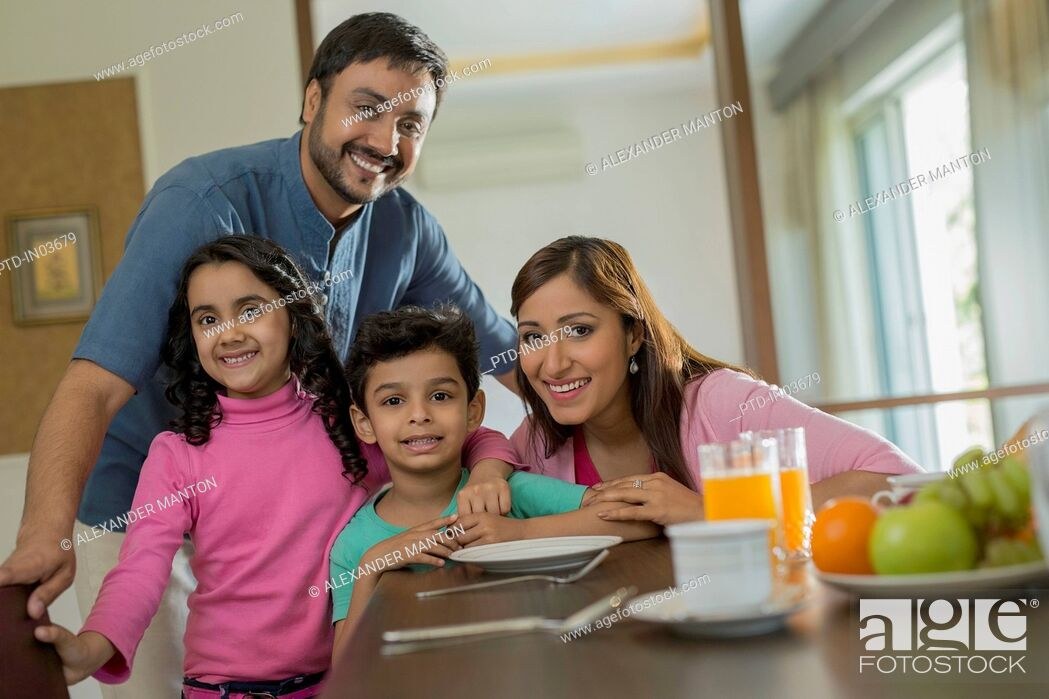 Stock Photo: Man and woman with two children at dining table.
