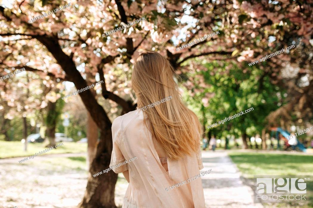 Stock Photo: Blond haired woman by blossoming trees.
