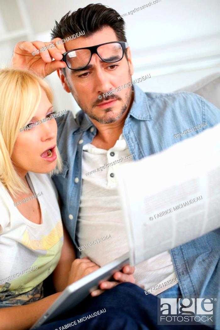 Stock Photo: Couple reading news with horrified look.
