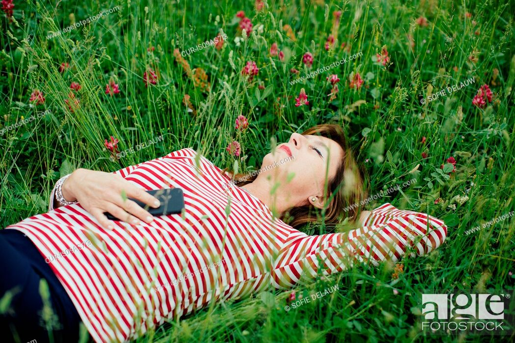 Imagen: Mature woman lying on grass holding smartphone.