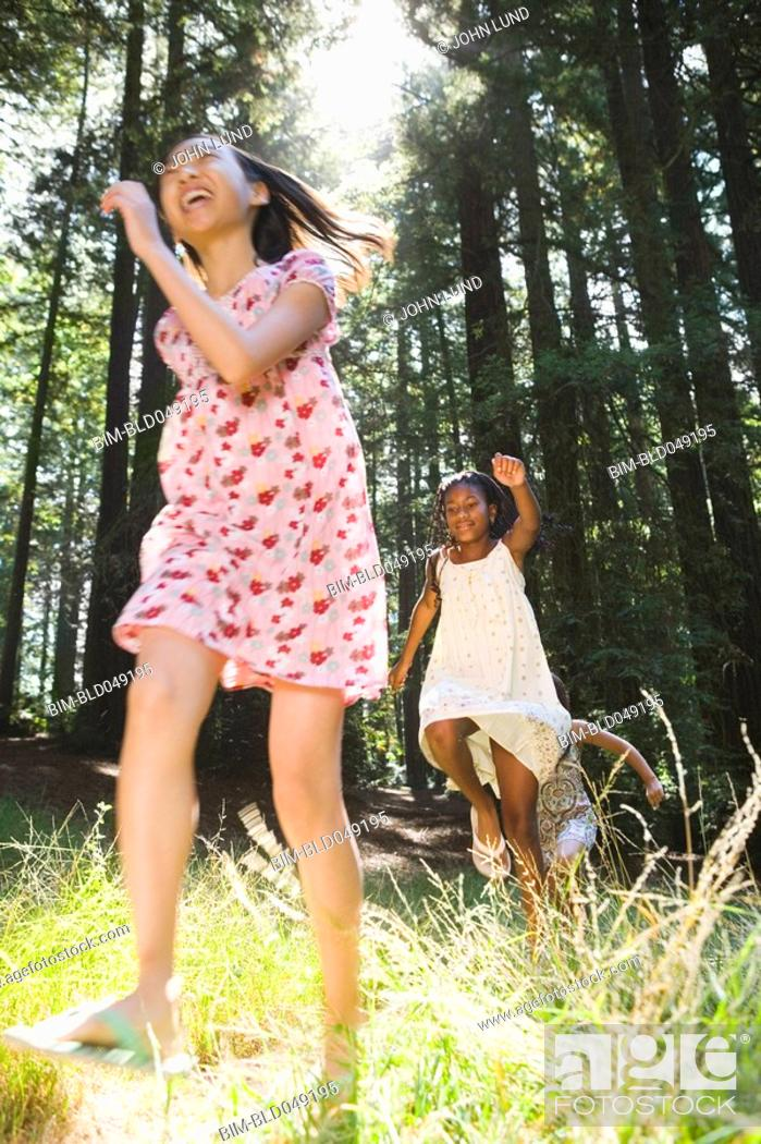 Stock Photo: Multi-ethnic girls running in woods.