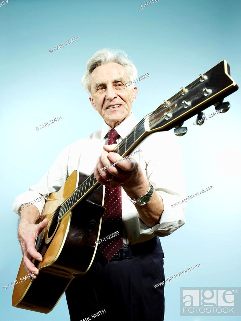 Stock Photo: A senior man playing an acoustic guitar.