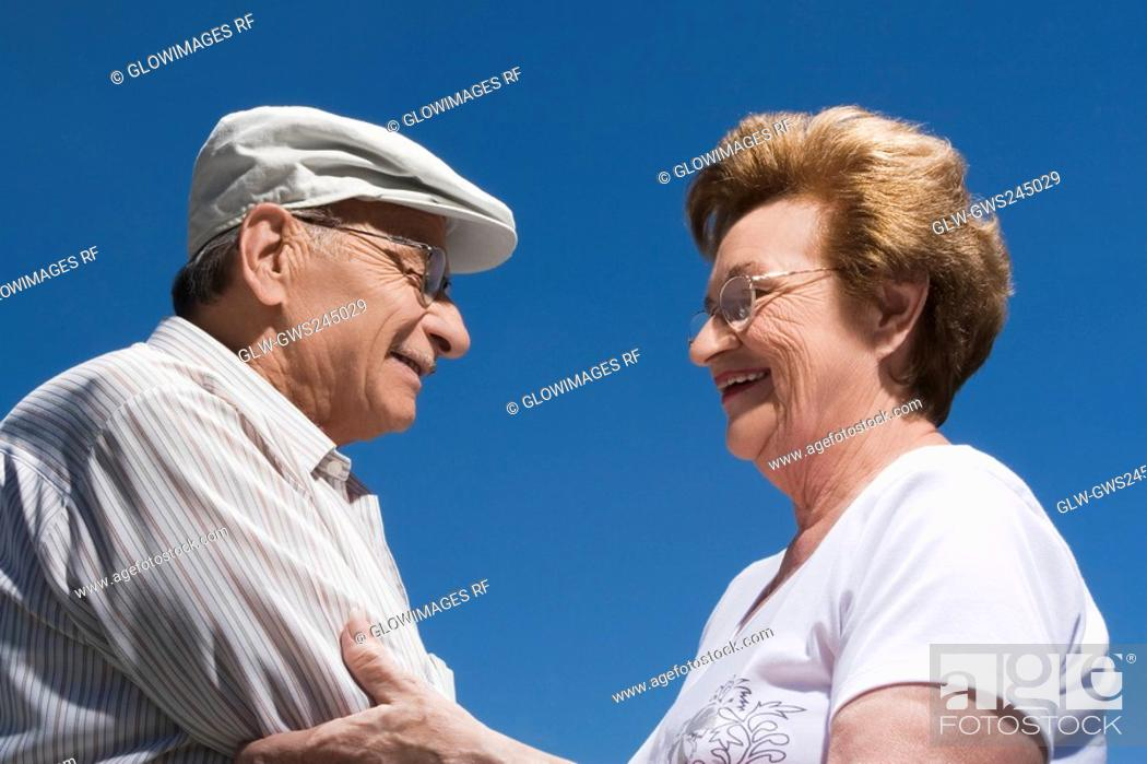 Stock Photo: Side profile of a senior couple holding each other and smiling.