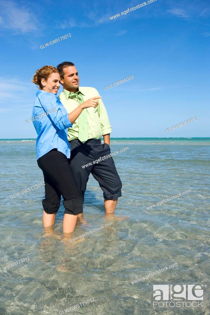 Stock Photo: Mid adult couple standing in water.