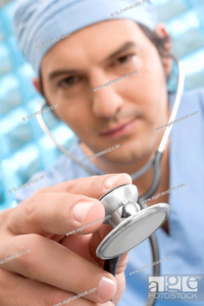 Stock Photo: Male surgeon holding a stethoscope.