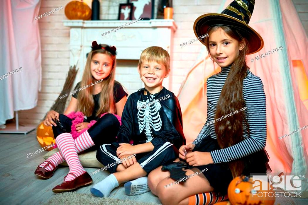 Stock Photo: Portrait of three children wearing Halloween costumes posing looking at camera sitting on floor in decorated studio.