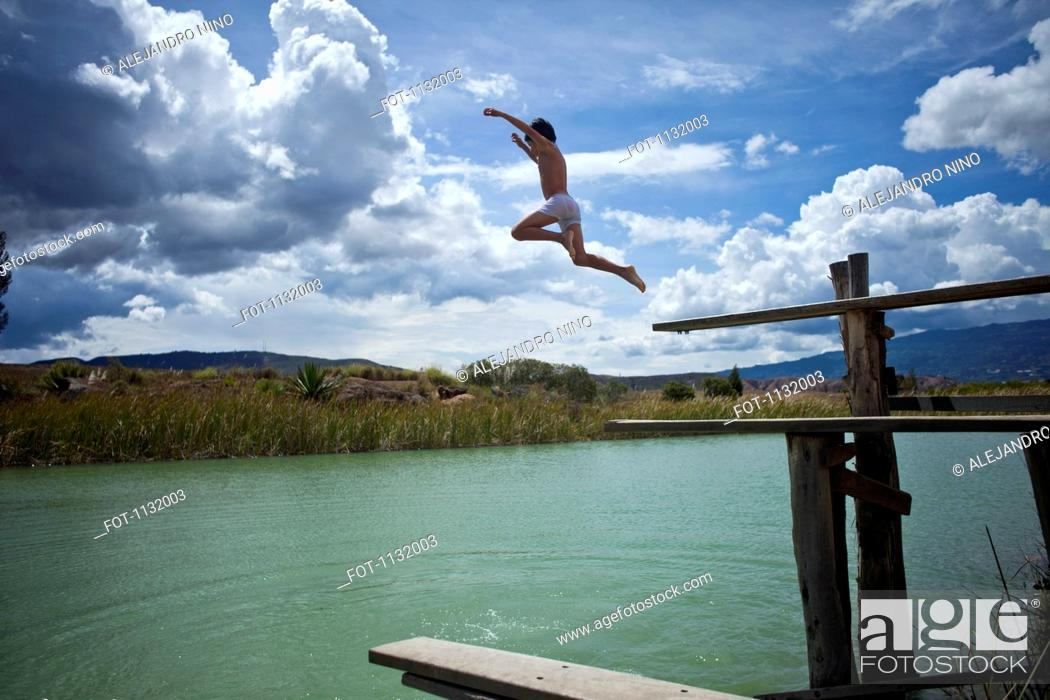 Stock Photo: A young boy jumping into a lake.