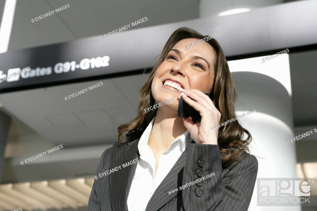 Stock Photo: Young businesswoman on the phone in airport.