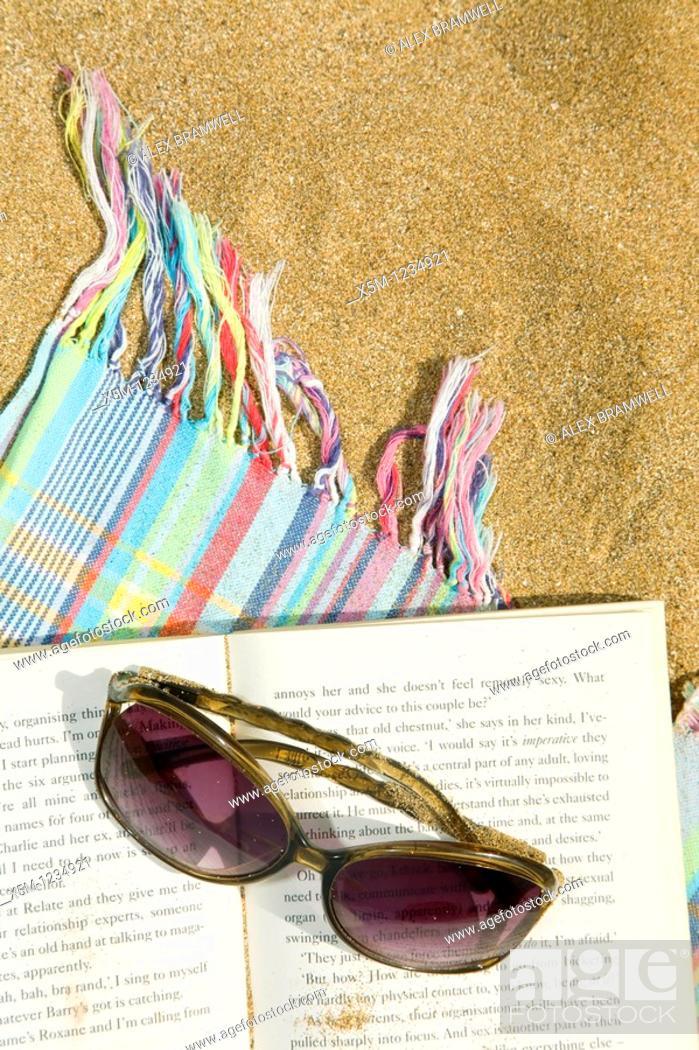 Stock Photo: Sunglasses and novel on a beach towel.