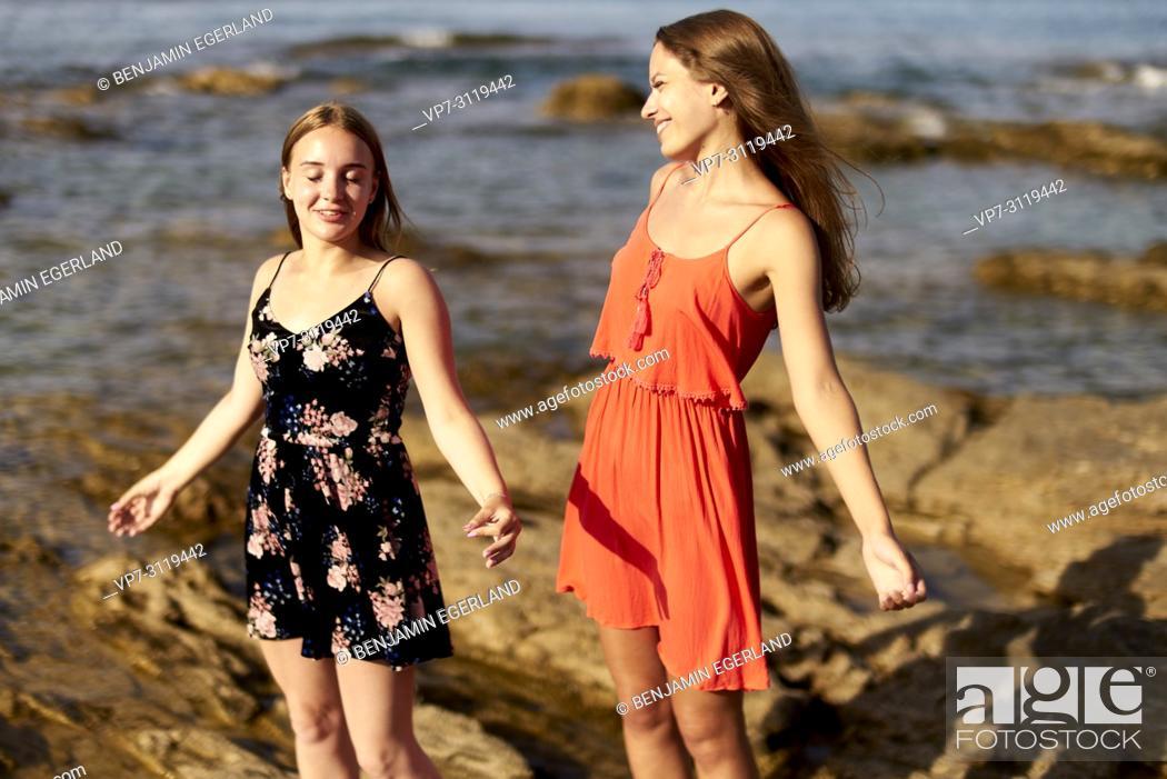 Photo de stock: two women, friends, standing at beach two women, friends, at beach, togetherness in holiday destination Chersonisoss, Crete, Greece.