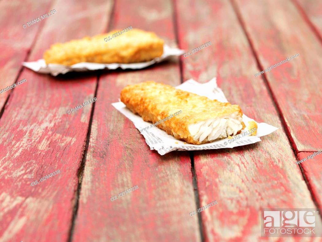 Stock Photo: Two fried chunky battered cod pieces on red wooden table.