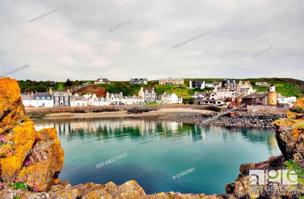 Stock Photo: Tranquil view of Portpatrick harbour in southwest Scotland, lined with pretty houses and framed by lichen covered rocks in the foreground.