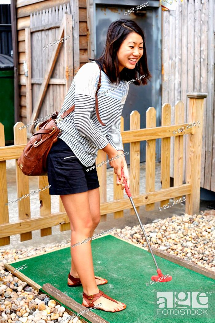 Stock Photo: Young woman playing crazy golf.