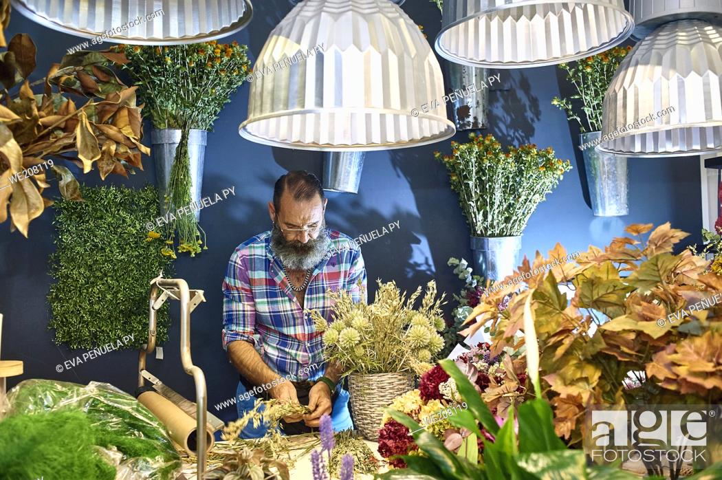 Photo de stock: A florist taking care of various flowers and bouquets in his shop.