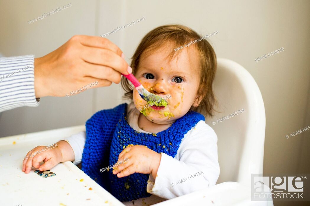 Stock Photo: Mother feeding baby girl in high chair.