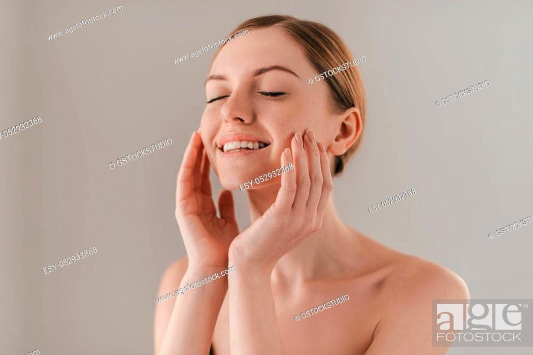 Stock Photo: Enjoying the softness of her skin. Studio portrait of attractive woman with freckles on face touching her skin and keeping eyes closed while standing against.