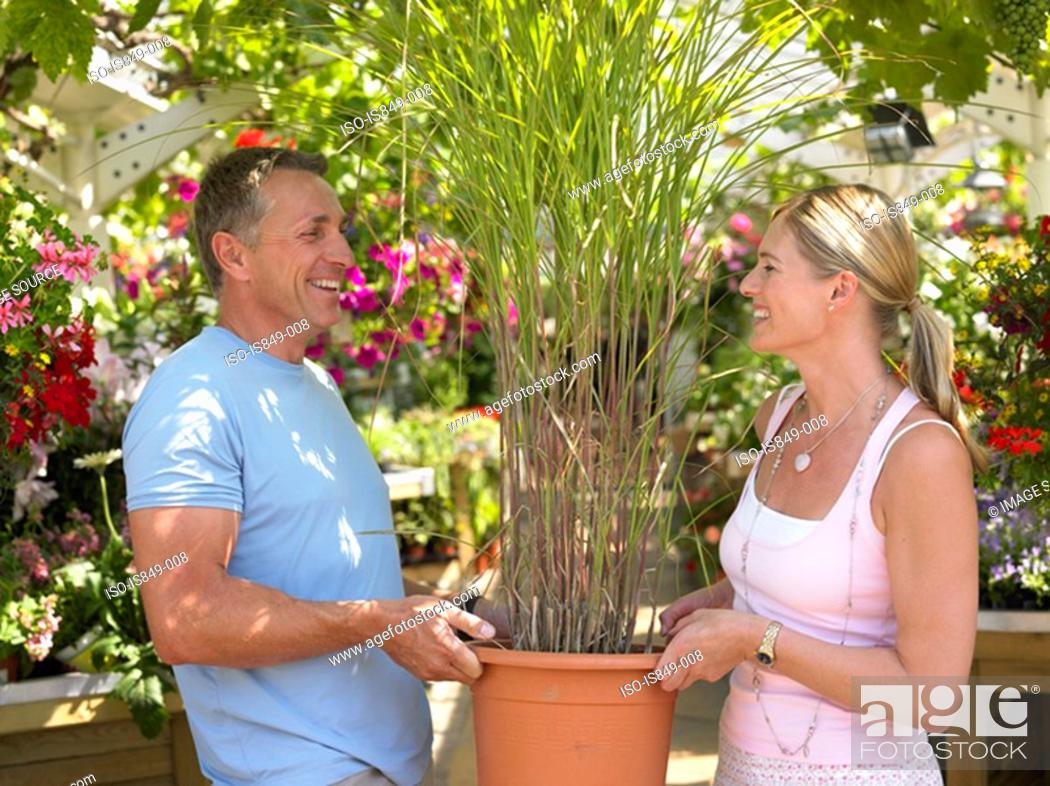 Stock Photo: Couple carrying a plant in garden centre.