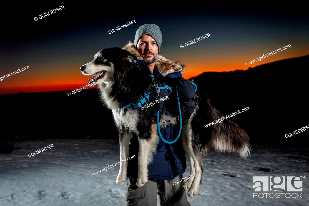 Imagen: Portrait of mature man carrying dog in snow at night.