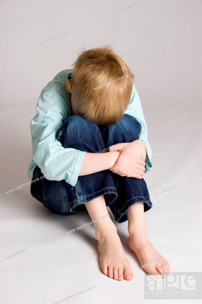 Stock Photo: A young boy sits hunched over hugging his bent legs and hiding his face.