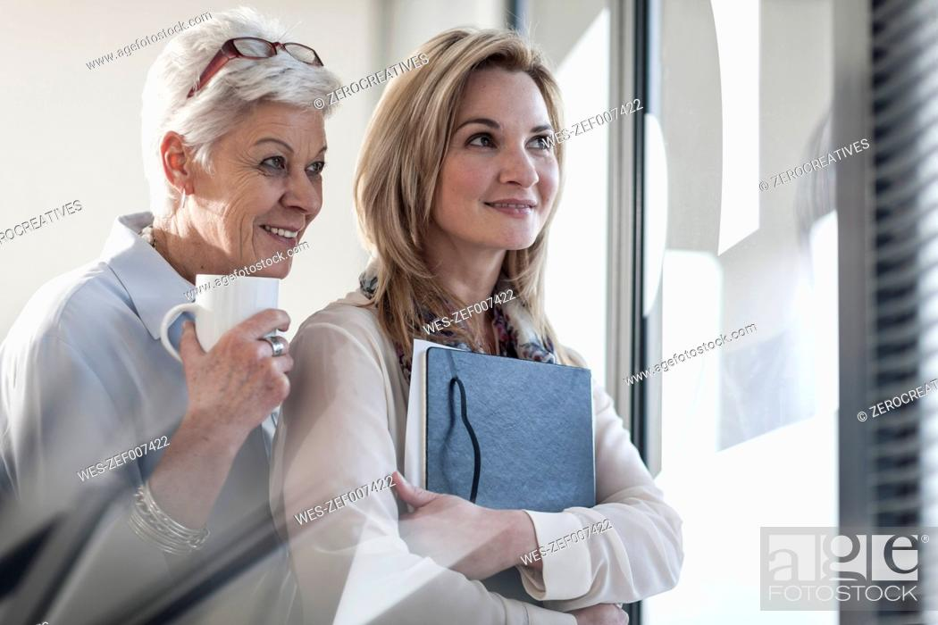 Stock Photo: Two women in office looking through blinds.