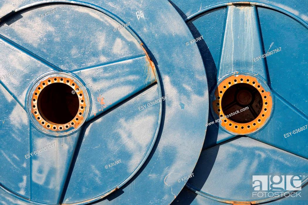 Stock Photo: Two big metal spools with hole for drive shaft.