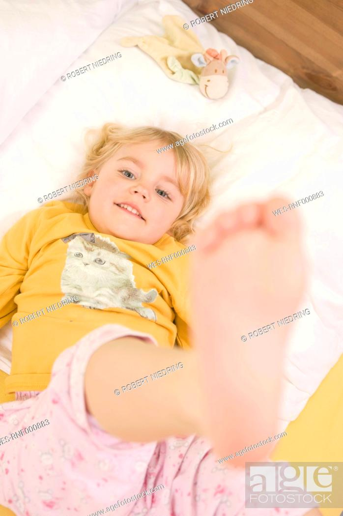 Stock Photo: Girl lying on bed, smiling, portrait.