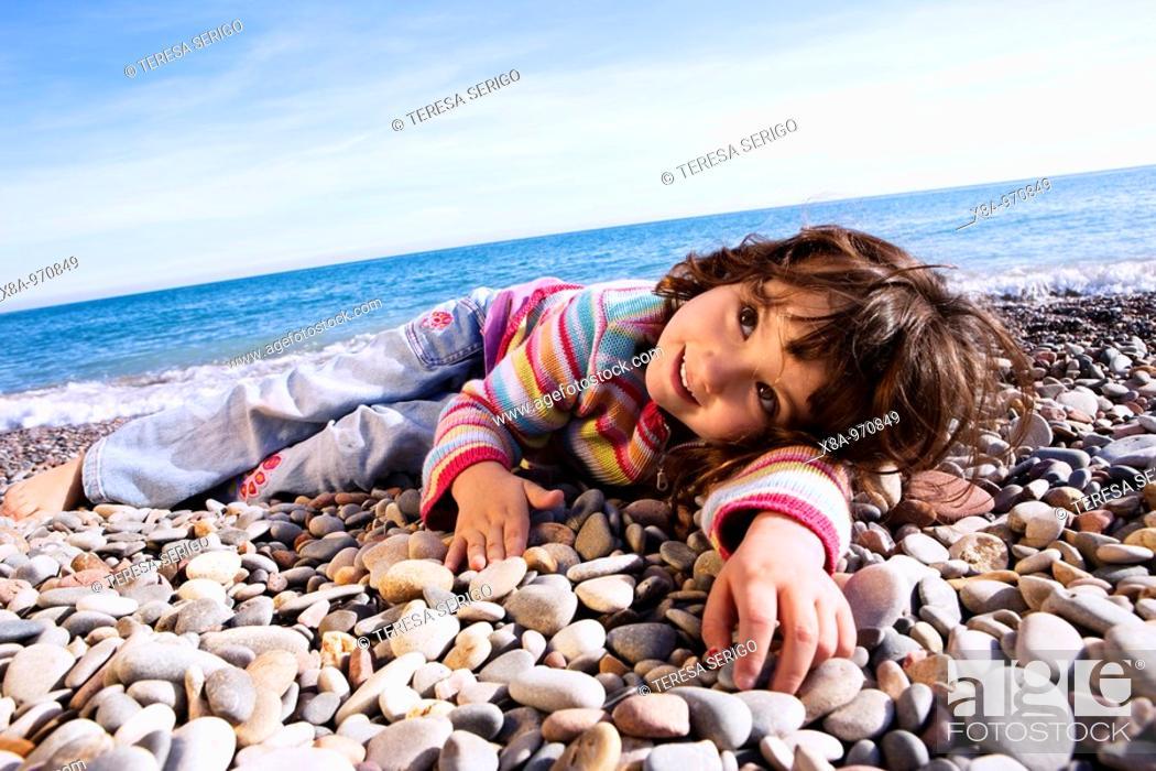 Stock Photo: baby girl lying on the beach.