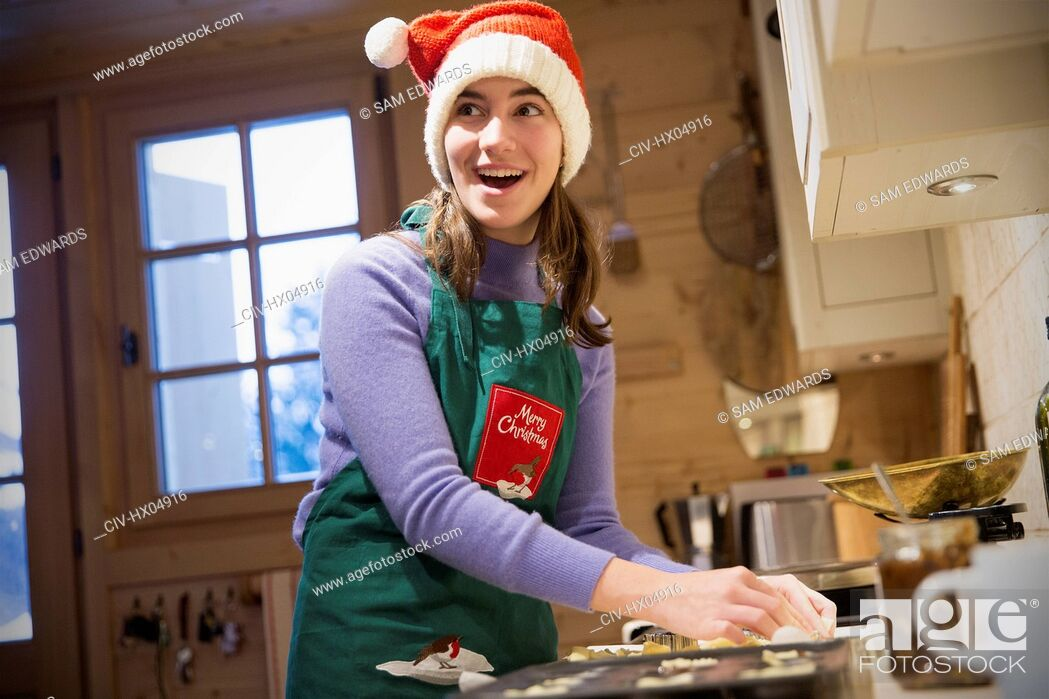 Stock Photo: Smiling teenage girl in Christmas apron and Santa hat baking in kitchen.