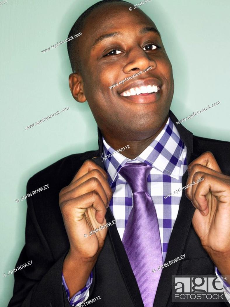 Stock Photo: Businessman holding lapels in studio head and shoulders.