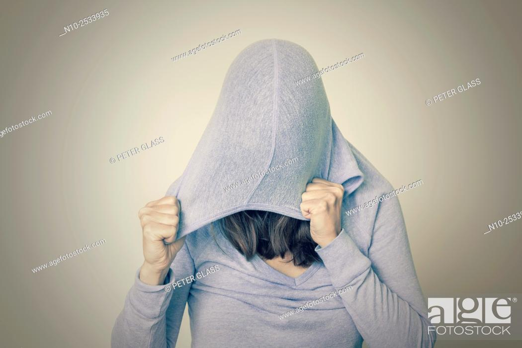 Stock Photo: Young woman wearing a hood.