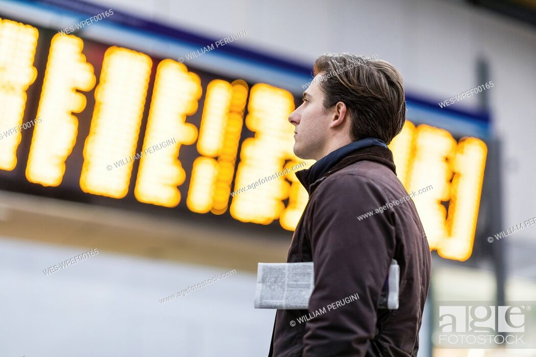 Stock Photo: UK, London, businessman at train station looking at timetable.