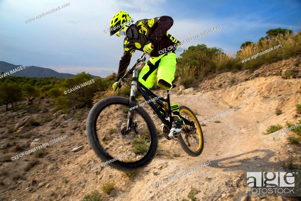 Stock Photo: Invisible downhill ghost mountain biker riding on a trail in Spain.