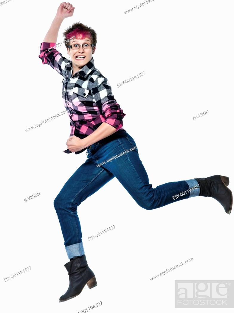 Stock Photo: Full length of a casual young expressive woman running in studio on white isolated background.