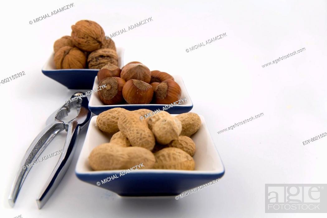 Stock Photo: walnuts, hazelnuts and peanuts in three bowls.