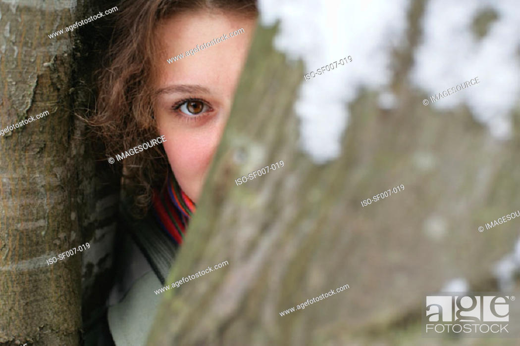 Stock Photo: Young woman hiding behind tree.