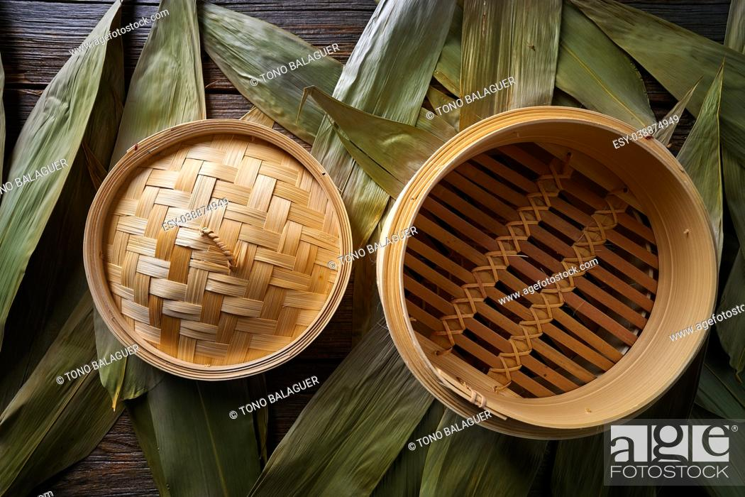 Stock Photo: Asian kitchen bamboo steamer for steam cooking recipes on leafs.