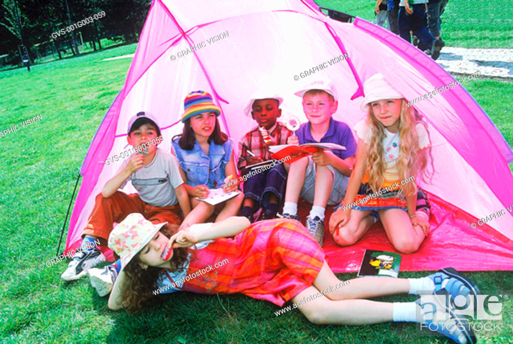 Stock Photo: Young children sitting in a tent with candy.
