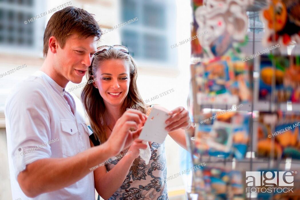 Stock Photo: Smiling couple examining postcards.