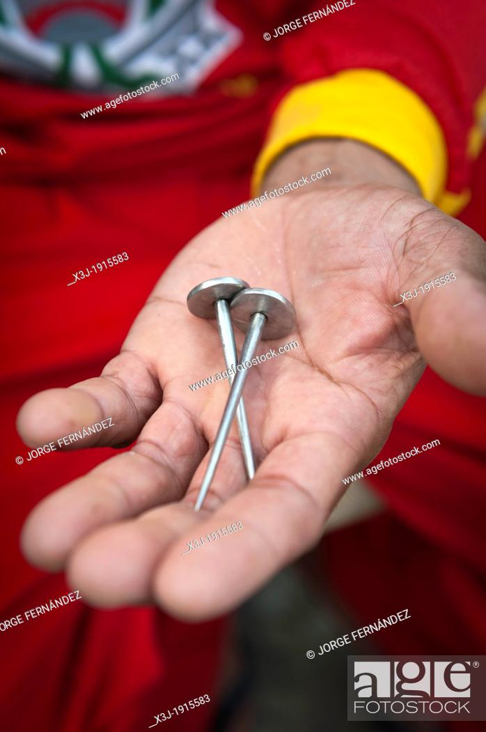 Stock Photo: Rolly showing the nails that will be used for his crucifixion on Good Friday, San Fernando, Pampanga, Philippines.