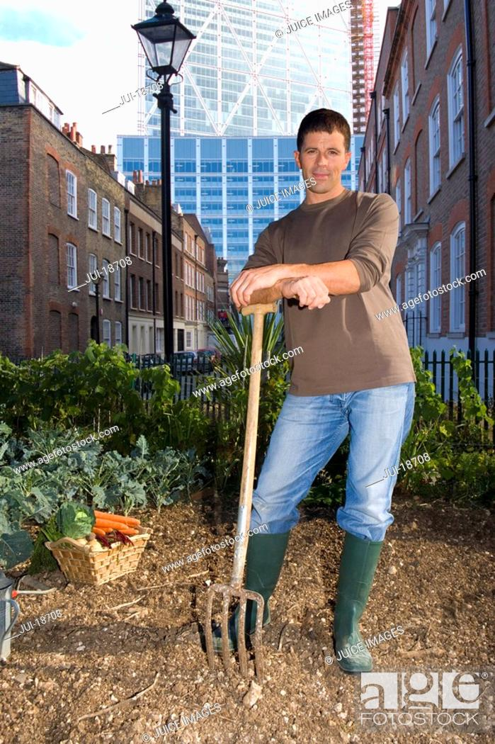 Stock Photo: Man posing with pitchfork in urban rooftop garden.